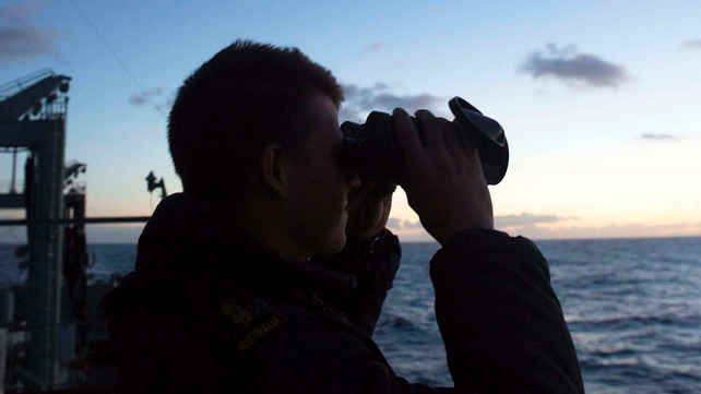 A member of the Royal Australian Navy ship HMAS Success has an early morning lookout in the search for Flight MH370