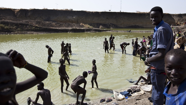 Men and children gather to bathe at a pool of water near the UN Mission in South Sudan