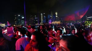 Fans of 'The Amazing Spider-Man 2' wait for the start of the dimming of lights for Earth Hour with the Singapore business district skyline in the background