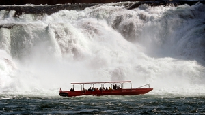 People enjoy a trip to the Rheinfall waterfall in Neuhausen, Switzerland