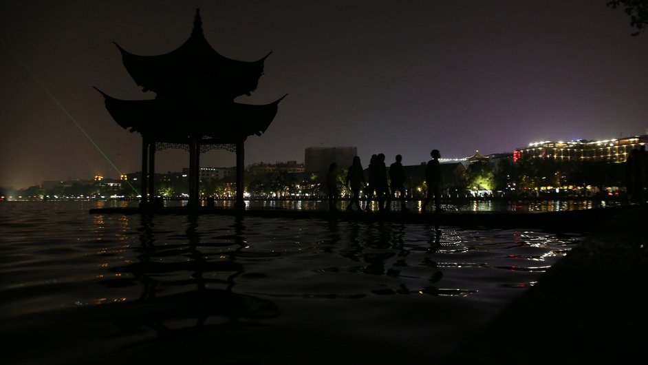 Tourists stand in a pavilion at the West Lake in Hangzhou city in China's Zhejiang province