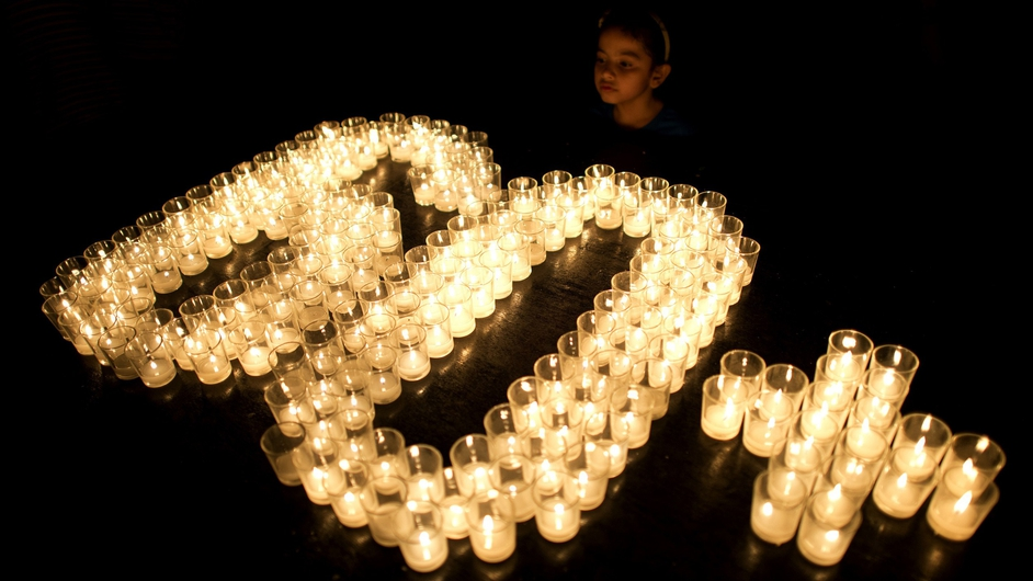 A child looks on at lit candles to mark Earth Hour in Manila