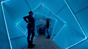 Visitors inspect an installation as part of the art of lighting festival in Frankfurt, Germany