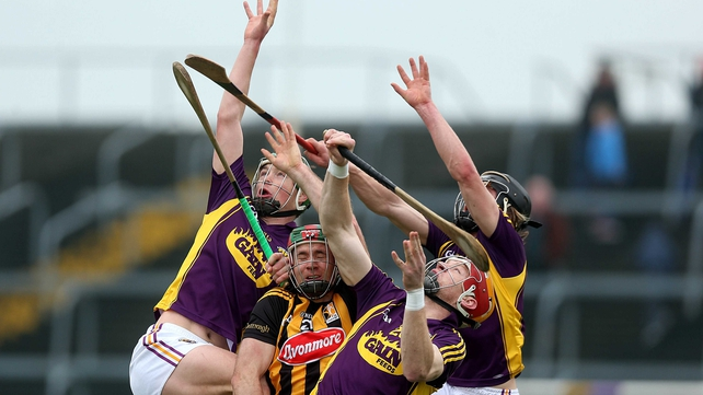 Wexford and Kilkenny players await a dropping ball