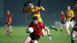 Down's Conor Maginn takes the ball and falls with Andrew Tormey nearby