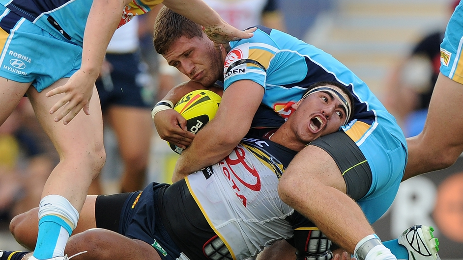 Andrew Niemoeller of the North Queensland Cowboys is tackled by players Gold Coast Titans in an Australian rugby league game