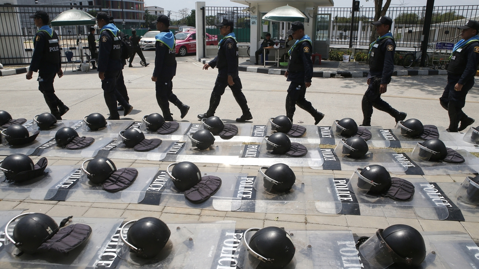 Thai police patrol past riot helmets and shields at the office of the National Anti-Corruption Commission building (Pic: EPA)