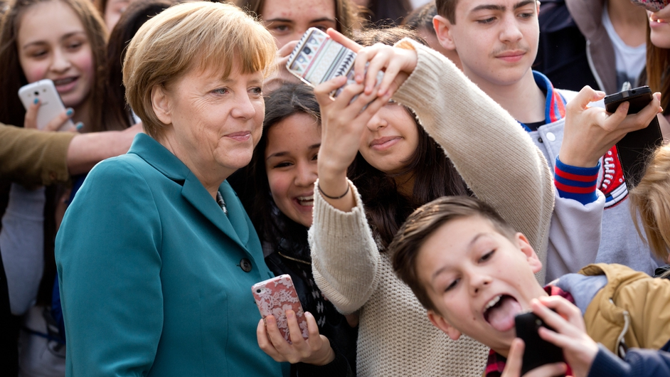 German Chancellor Angela Merkel poses for a 'selfie' with young students in Berlin (Pic: EPA)