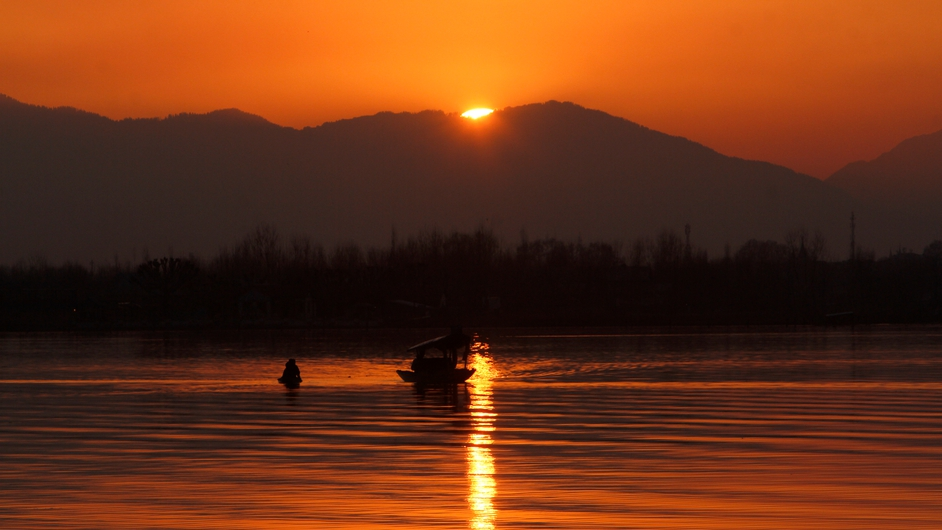 The setting sun dips down behind a mountain range sending a golden glow over Kashmiri boatmen as they row their Shikaras (gondolas) on the Dal Lake in Srinagar, the summer capital of Indian Kashmir (Pic: EPA)