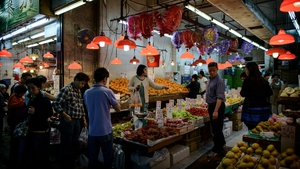 People shop for fresh fruit in a street market in Hong Kong