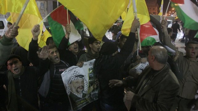 Palestinian supporters of the Fatah movement wave their national flag and the party's flag as they demonstrate in support of the Palestinian president Mahmud Abbas