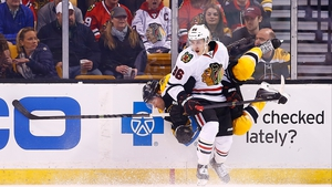 Teuvo Teravainen hits Johnny Boychuk of the Boston Bruins during the game in Boston, Massachusetts