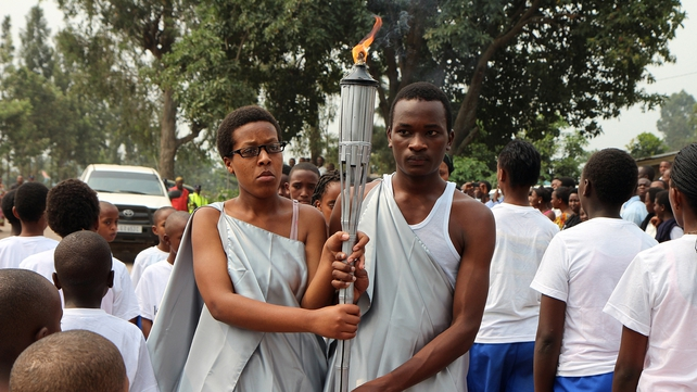Two 20-year-old youths carry the 'flame of remembrance', which is making a tour of Rwanda this year