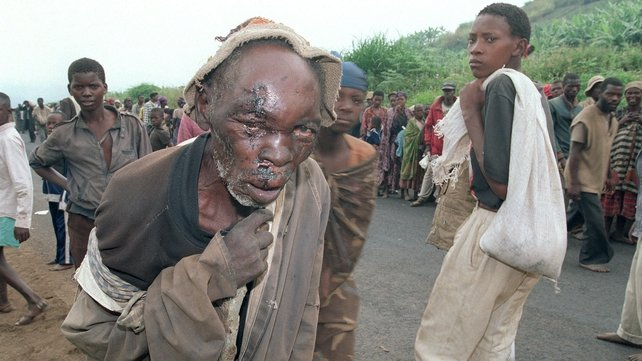 A seriously wounded Rwandan refugee follows hundreds of other displaced people in July 1994, near the city of Gikongoro