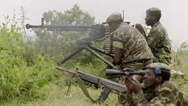 Rwandan government soldiers fire heavy artillery at rebel positions as a third man watches in June 1994