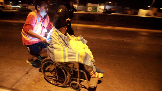 An elderly resident in Antofagasta is rushed from her home following further earth tremors