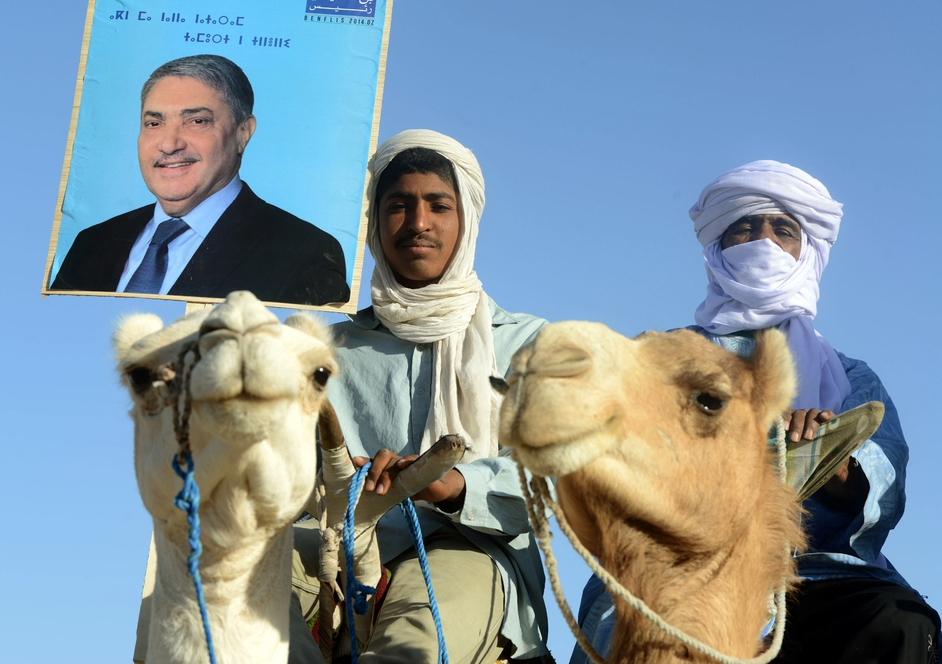 Supporters of Algerian presidential candidate Ali Benflis hold up his image