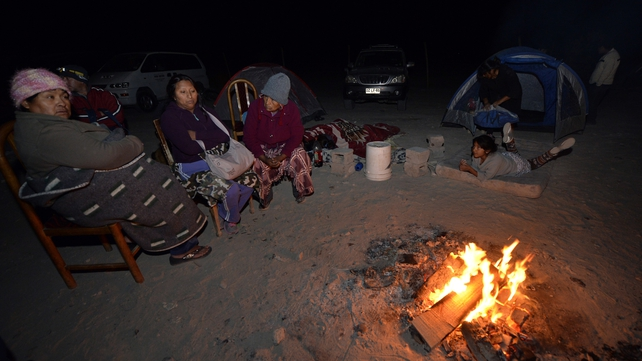 Residents from Pozo al Monte gather around a camp fire