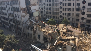 Firefighters search for survivors after an apartment building collapsed in the Zhejiang Province of China