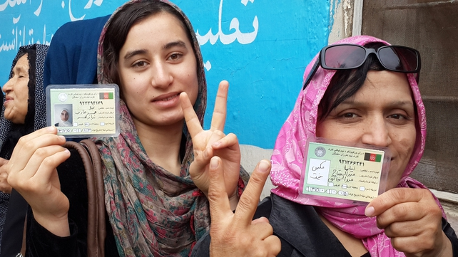 Two Afghan women show their voter registration cards outside a polling station (Pic: EPA)