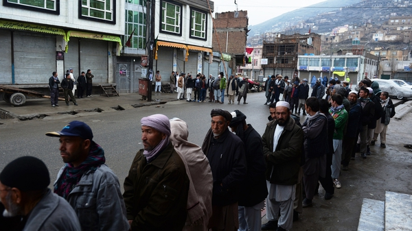 Afghan voters line up outside a local polling station in Kabul