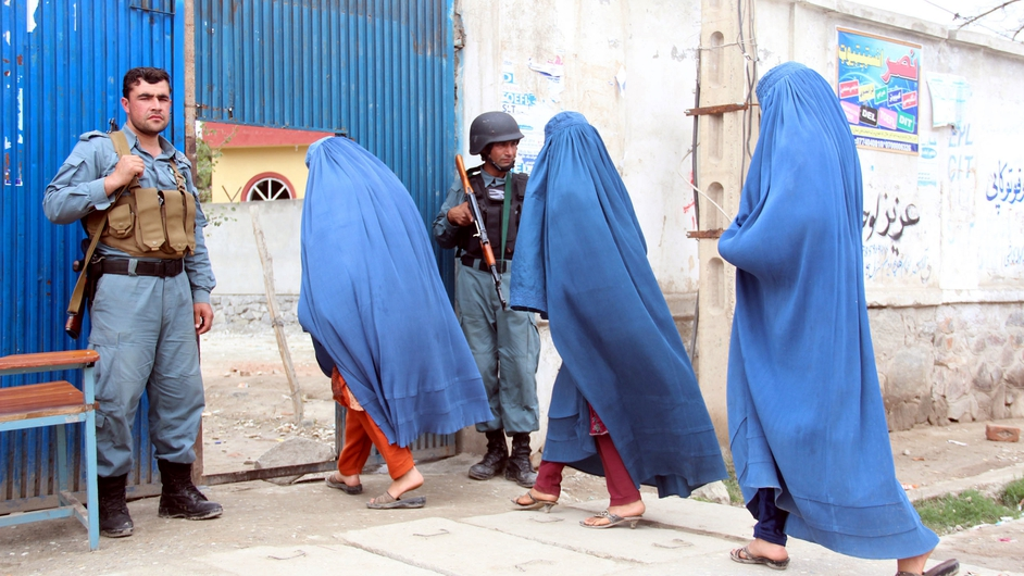 Afghan women walk past soldiers as they cast their votes in the presidential election (Pic: EPA)