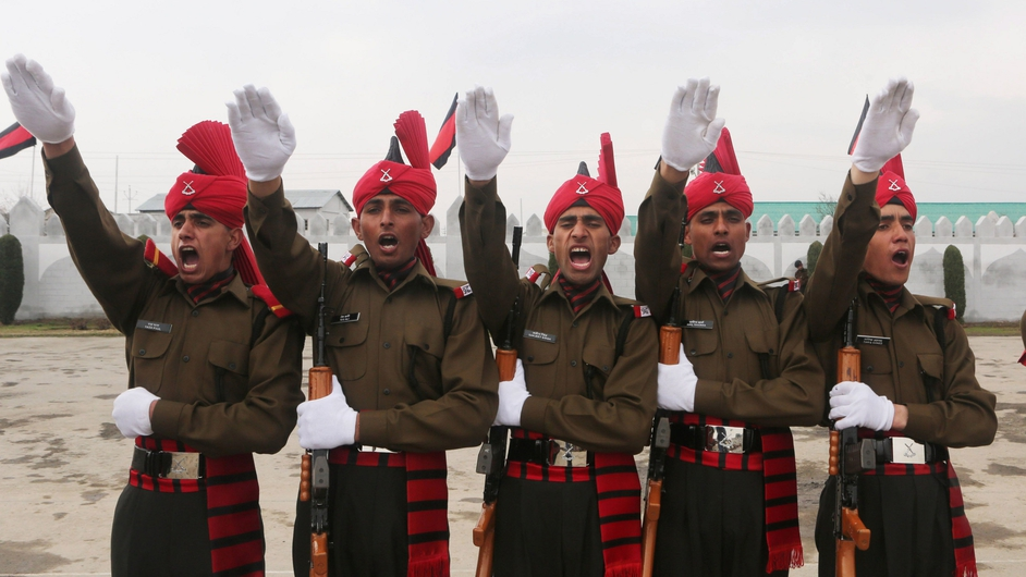 New recruits of the Jammu and Kashmir Light Infantry Regiment stand to attention during the passing out parade at an Indian Army in Srinagar