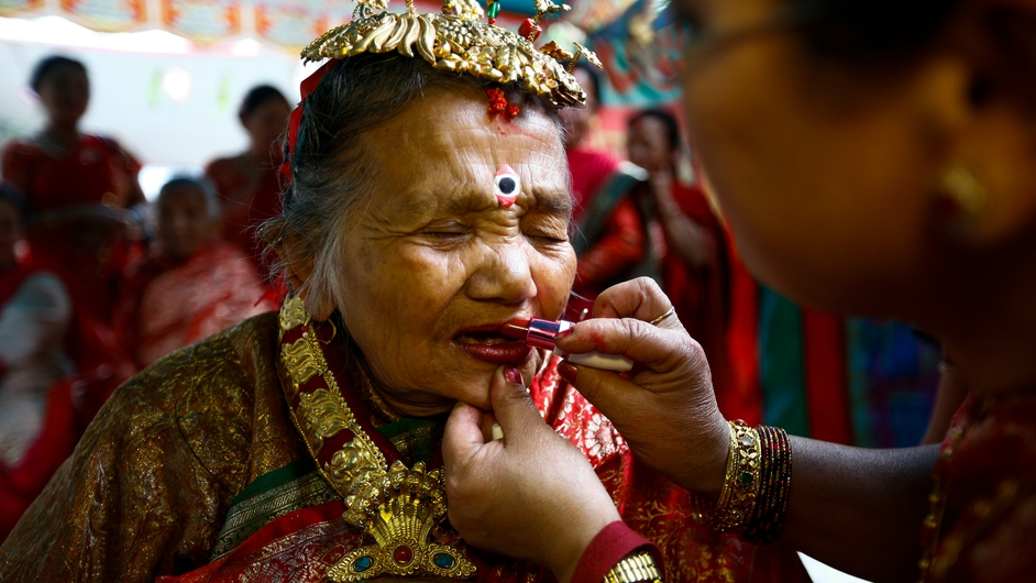 Relatives make-up elderly Nepalese woman Laxmi kumari Manandhar during preparations for 'Janku' tradition in Kathmandu (Pic: EPA)