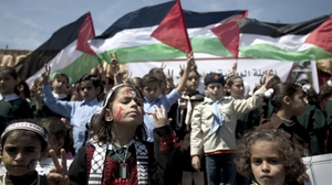 Palestinian children flash the 'V-sign' for victory and hold national flags during a demonstration demanding for the lifting of the Israeli blockade on the Gaza Strip and marking the Palestinian children's Day