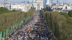 Competitors run on the Champs Elysees at the start of the Paris Marathon