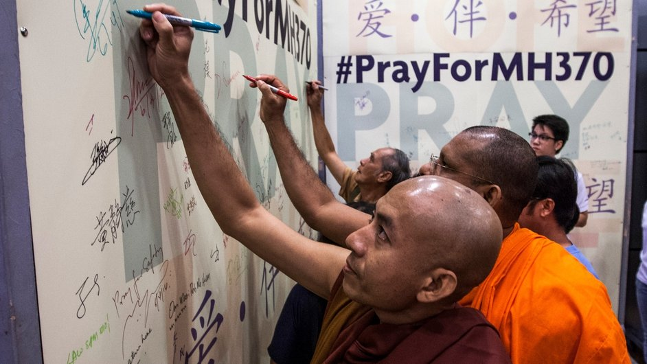 Monks write messages before a mass to remember the passengers and crew of Malaysian Airlines Flight MH370