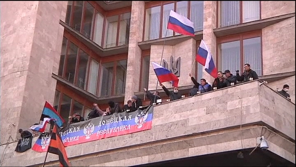 The activists raised a Russian flag over the building after similar protests in the eastern cities of Donetsk and Lugansk