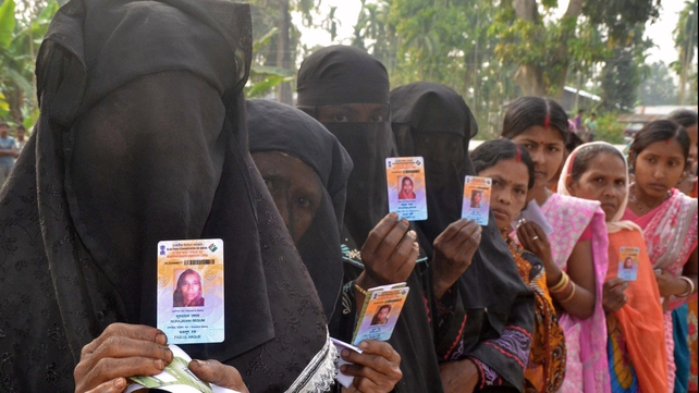 Indian Muslim voters pose with identification as they wait in line to vote outside a polling station in Koliabor