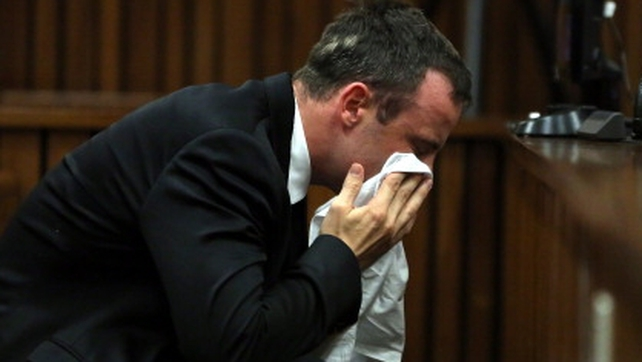 Oscar Pistorius wipes his face during his trial in court in Pretoria today