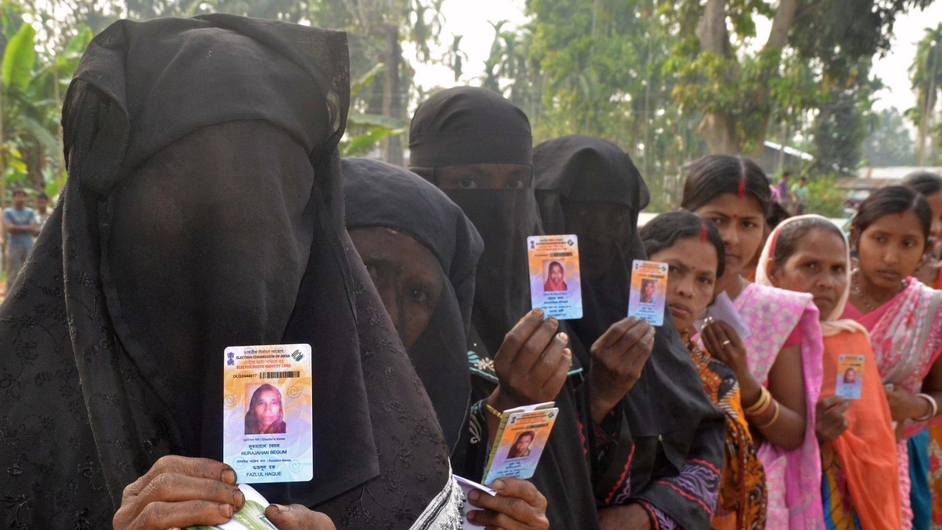 Voters show identification as they wait outside a polling station in Koliabor, India