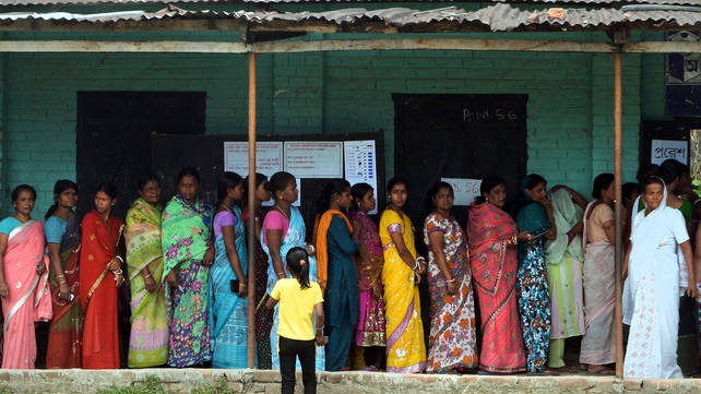 Voters wait in line outside a polling stating in Dibrugarh