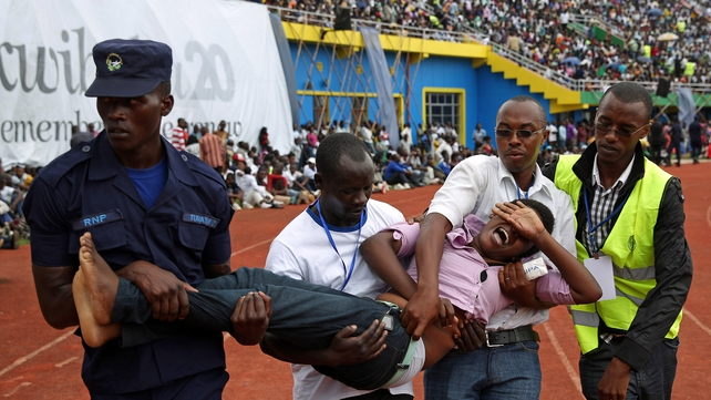 An emotional woman is carried out of the ceremony at Amahoro Stadium in Kigali