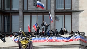 Pro-Russia activists fly Russian flags and the flag of the recently proclaimed Donetsk Republic