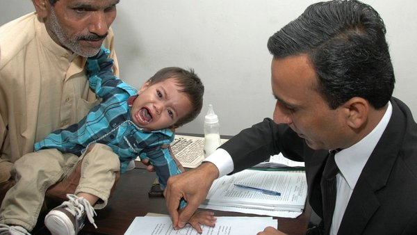 A Pakistani lawyer takes the thumb impression from the nine-month-old baby