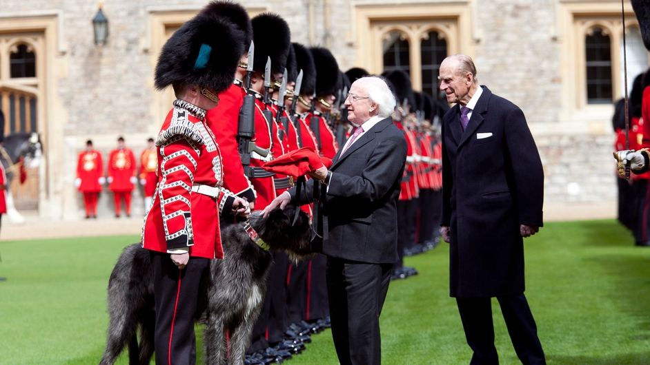 President Higgins presents a new ceremonial red coat to Domhnall of Shantamon, mascot of the Irish Guards