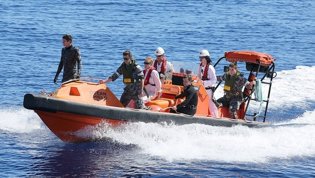Navy personnel search the ocean for debris of the missing flight