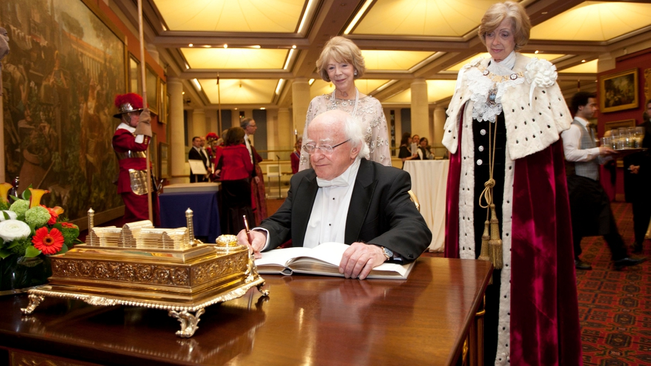 He signs a book at Guildhall in London in the presence of Mayor Woolf