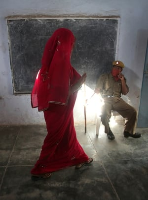 An Indian woman leaves a polling station after casting her vote in the village of Tigaon, India