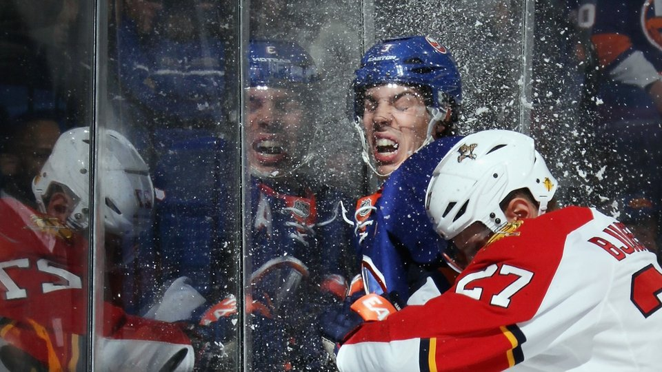 Travis Hamonic of the New York Islanders ice hockey team takes a hit from Nick Bjugstad of the Florida Panthers