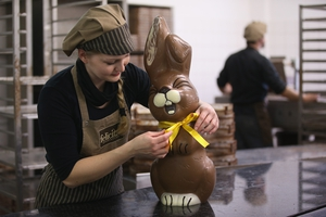 A worker puts the final touches to a chocolate Easter bunny at a factory in Germany