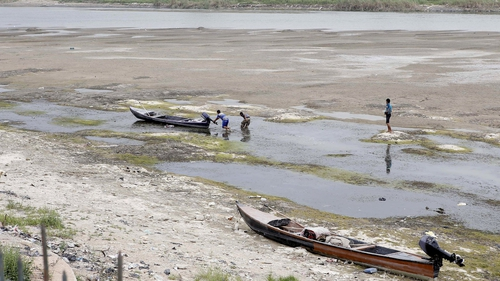Iraqi men move a boat that was stuck on the banks of the Euphrates in Twairij due to a decline in the water level