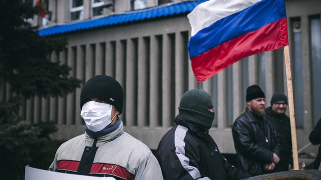 Masked Pro-Russia supporters stand guard outside the headquarters of Ukraine's security agency building in Lugansk