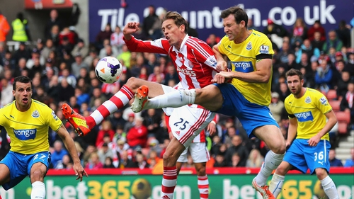 Stoke's Peter Crouch and Mike Williamson of Newcastle vie for posession