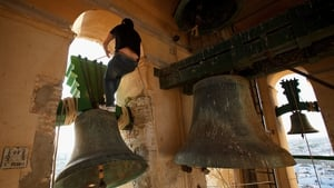 A bell ringer climbs on top of a bell as he performs on the eve of Palm Sunday in Santa Marta de la Mesa Church in Utrera, Spain