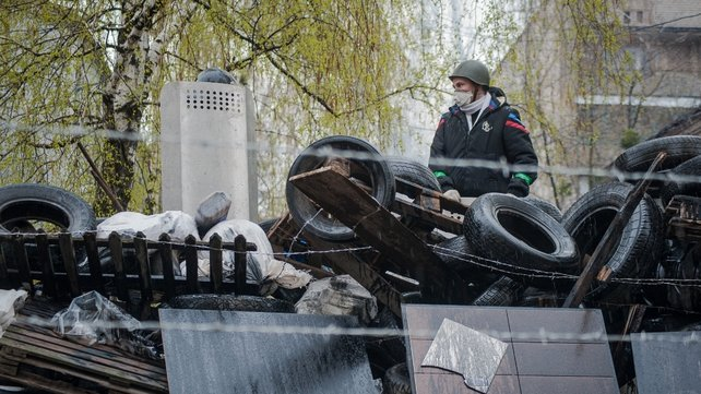 Pro-Russian protester stands on a barricade in front of the occupied police station (Pic: EPA)